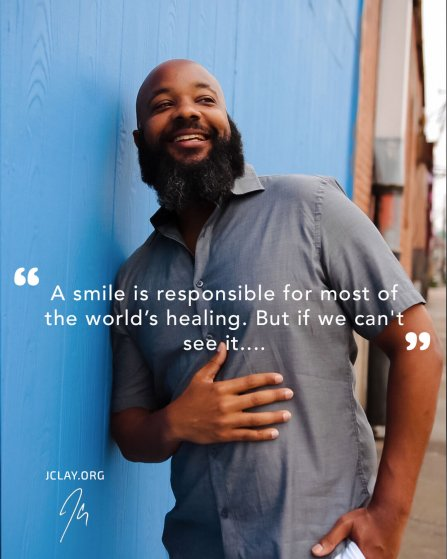 inspirational quote by jclay in front of blue wall with him smiling beard bald head