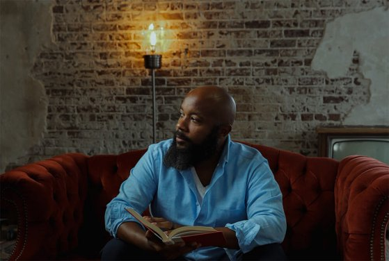 JClay in blue shirt holding a book on red couch with light bulb