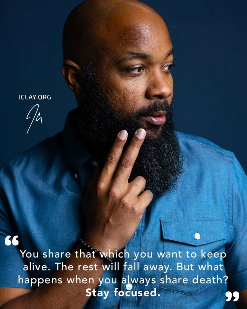 inspirational quote by jclay over an image of him wearing a teal shirt with 2 fingers held to beard