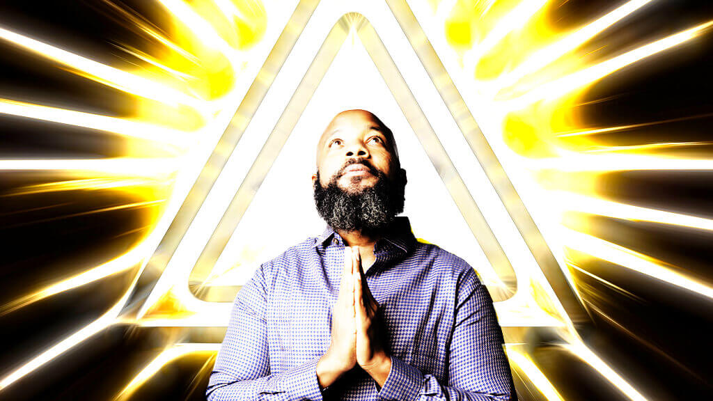 jclay brown praying hands with bright light triangle behind him