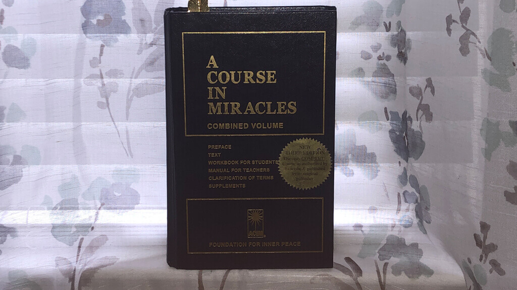 A Course In Miracles book on a window sill
