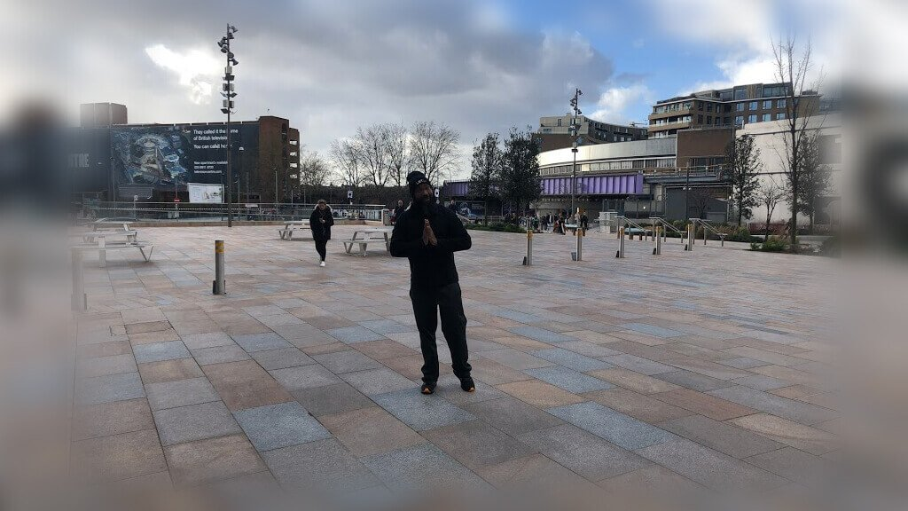 JClay with praying hands on a street in London